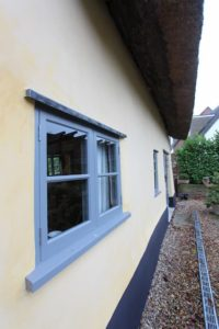 Lime render on the exterior of a thatched cottage with light blue windows